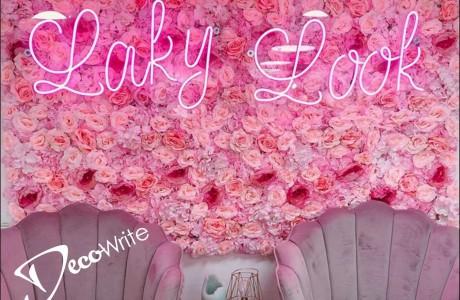 שלט לד גמיש צבע ורוד (LAKY LOOK) על גבי בסיס פרספקס שקוף (השלט מותקן על קיר פרחים)